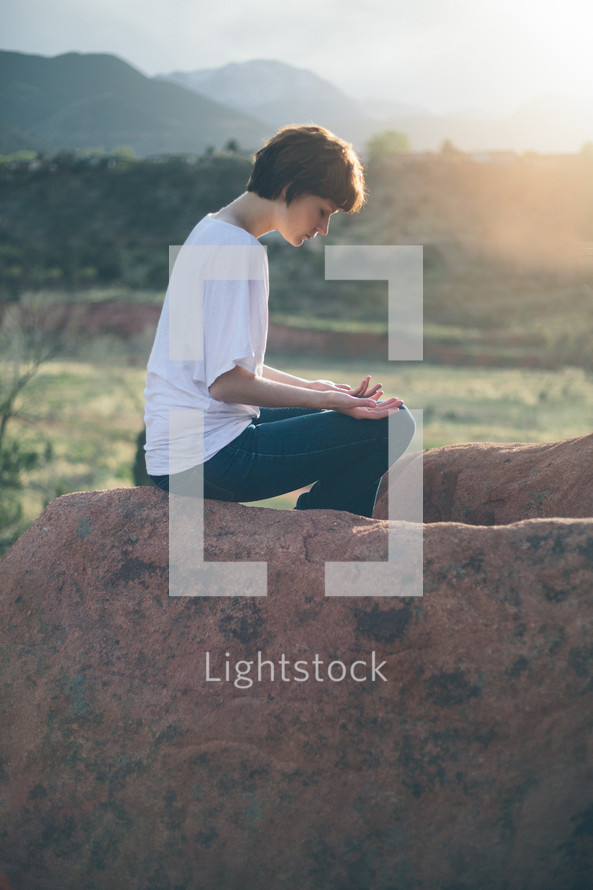 Woman sitting outside in prayer.
