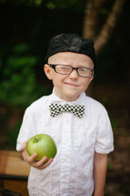 boy child in reading glasses and a hat winking holding an apple