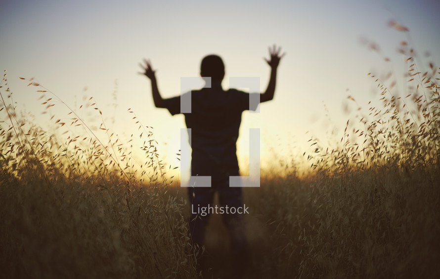 silhouette of a young man with raised hands at sunset