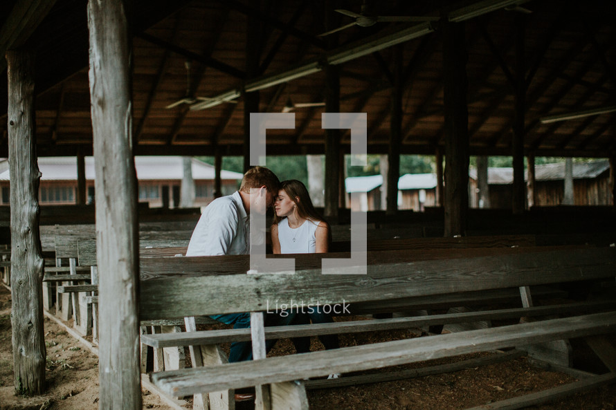 couple sitting in wooden pews outdoors