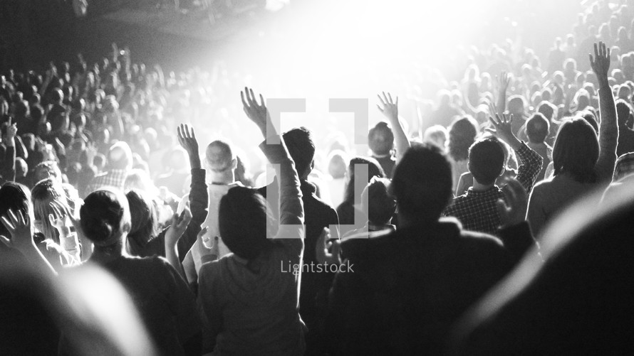 Hands raised in worship at a concert.