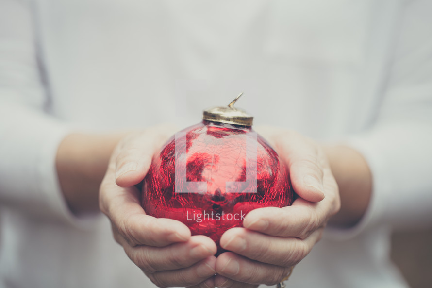 Hands holding a red Christmas ornament
