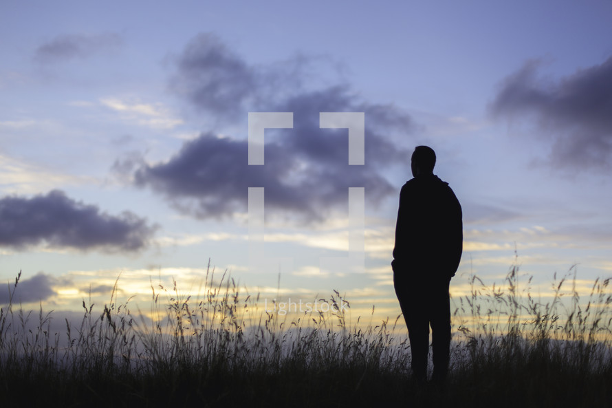 silhouette of a man standing in a field at sunset