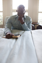a man in prayer at the side of a bed