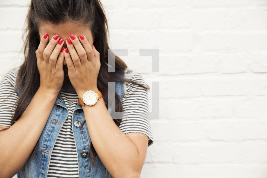 A woman standing against a white brick wall with her hands covering her face.