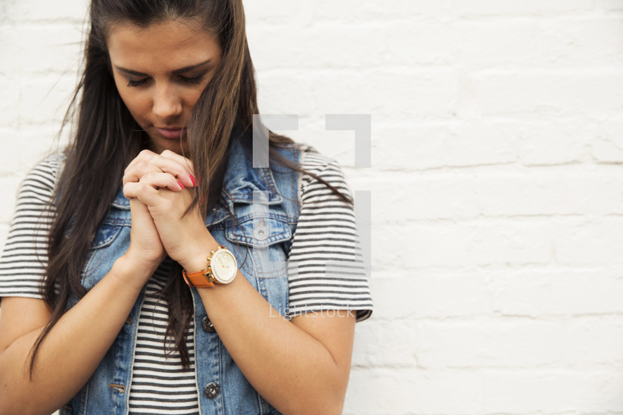 A woman standing against a white brick wall with her hands clasped in prayer.