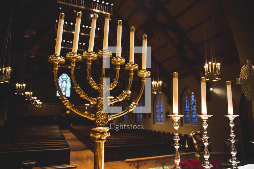 Candles and candelabra on the altar of an empty church.