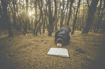 a man kneeling in prayer in front of a Bible in a forest