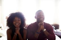 a joyful couple in prayer