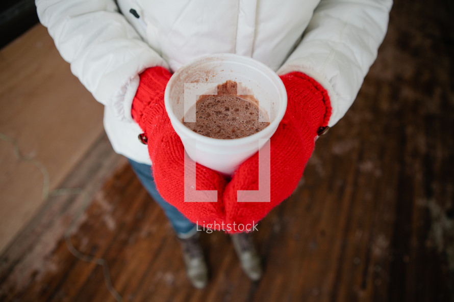 woman in mittens holding a cup of hot cocoa