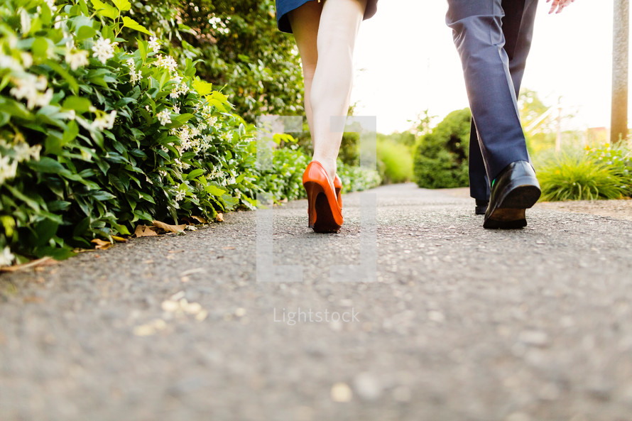 Couple's feet walking on a path.