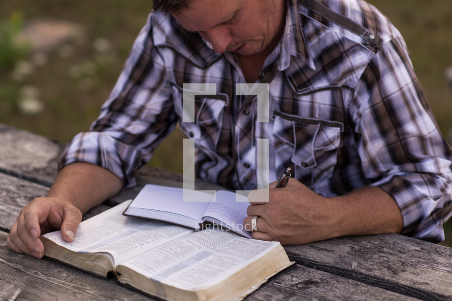 a man reading a Bible and writing in a journal at a picnic table outdoors