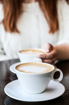 woman with her hand on a latte cup