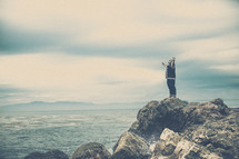 Man praising God on an ocean-side rocky cliff.