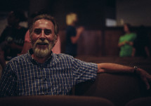 A bearded man sitting in a church auditorium.