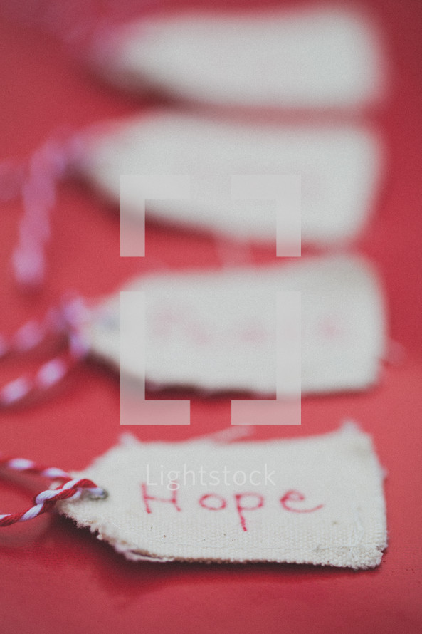 """Christmas gift tags, the first one reading """"Hope,"""" on a red background."""