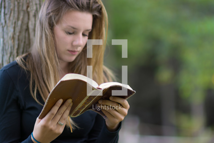 Girl sitting outside, leaning against a tree, reading a bible.