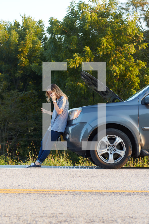 a woman on the phone next to a broken down vehicle