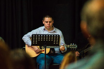 a man playing a guitar during a worship service
