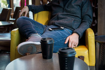 man with a cellphone on his lap sitting in a chair next to a coffee cup