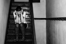 upset teen girl sitting on stairs