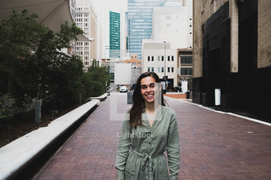 smiling woman standing downtown