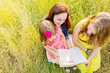 Mother and daughters sitting in tall grass reading the Bible.