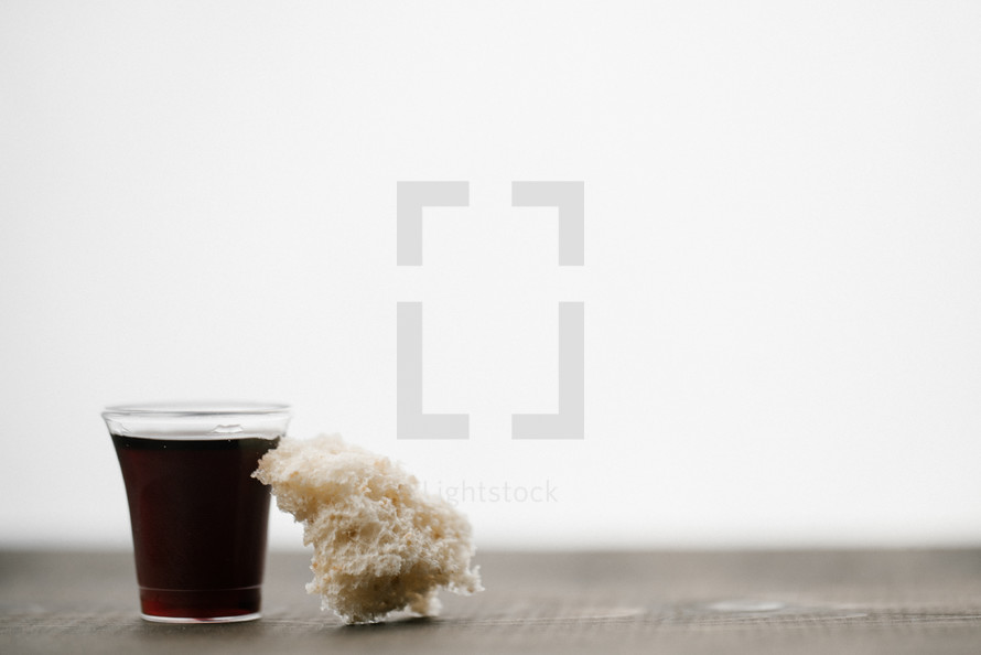 communion wine in a cup and bread on wood