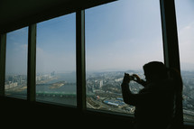 a woman taking a picture from a skyscraper window