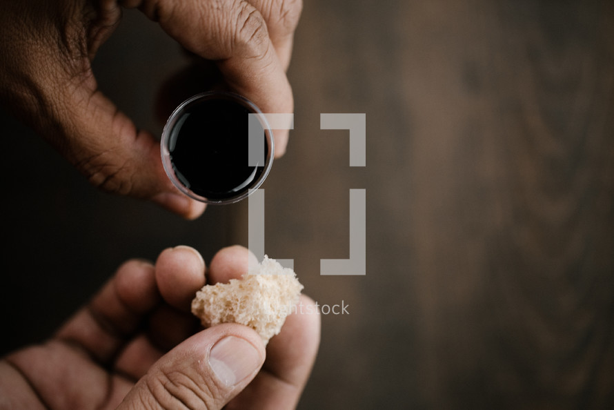 communion wine in a cup and bread on wood background