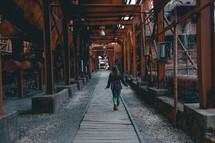 a woman walking under rusty steel beams