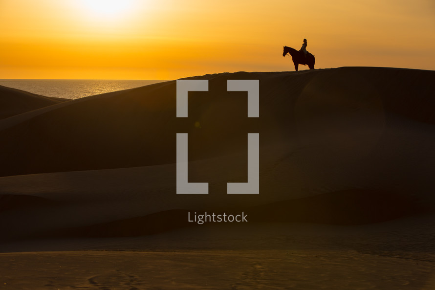 silhouette of a man on a horse on top of sand dunes
