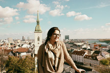 a woman standing in front of a view of a European city