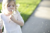 toddler girl blowing on a dandelion
