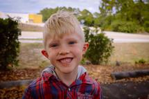 A smiling blonde boy.