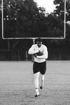 a man running with a football on a football field