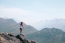 woman standing on rocks at the edge of a mountainside