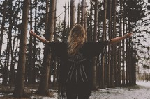 a woman with outstretched arms standing in a forest with fresh snow