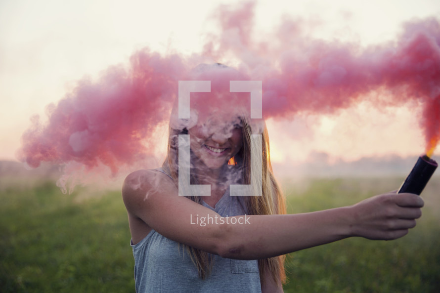 young woman holding a smoke flare