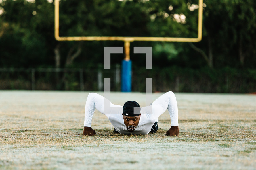 a man doing pushups on a sports field