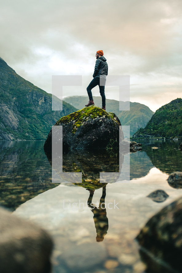 a man standing on a rock in the middle of a lake