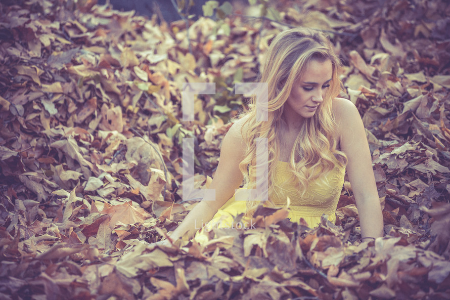 A woman lying in fall leaves.