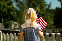 a girl child carrying an American flag