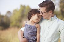 Daughter lovingly resting on her dad's shoulder.