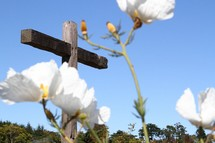 An outdoor wooden cross with white flowers in the foreground.