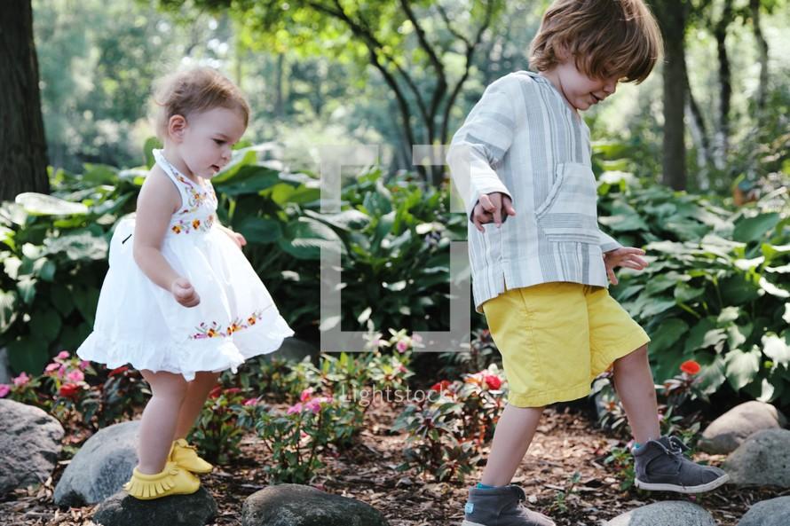 toddlers walking through a garden