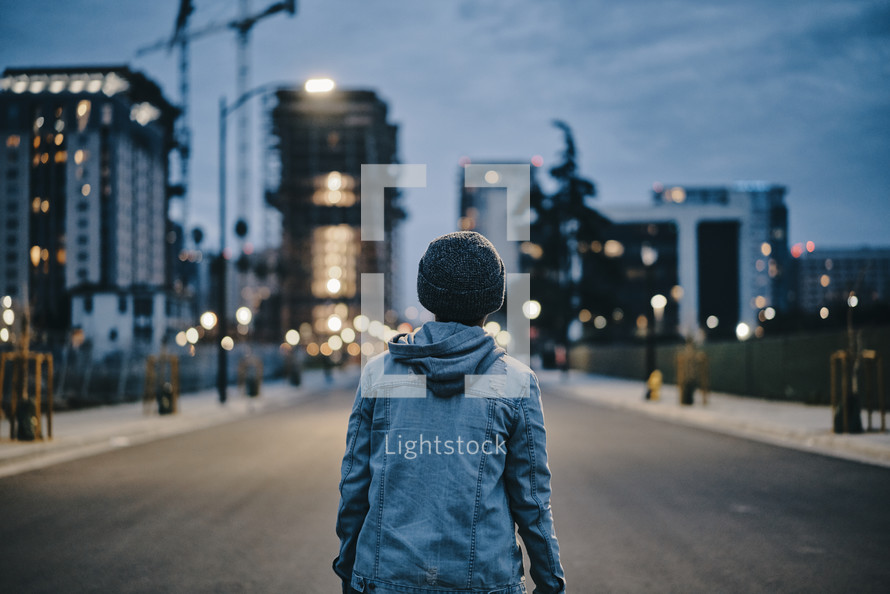 a teen boy standing in the middle of a road looking back at a city