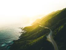 road along a green mountainous shoreline