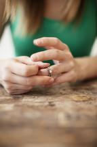A woman taking her wedding ring off her finger.