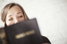 Woman intently reading Bible scripture.